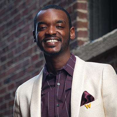 Headshot of DaQuan in front of brick wall in purple shirt and white jacket