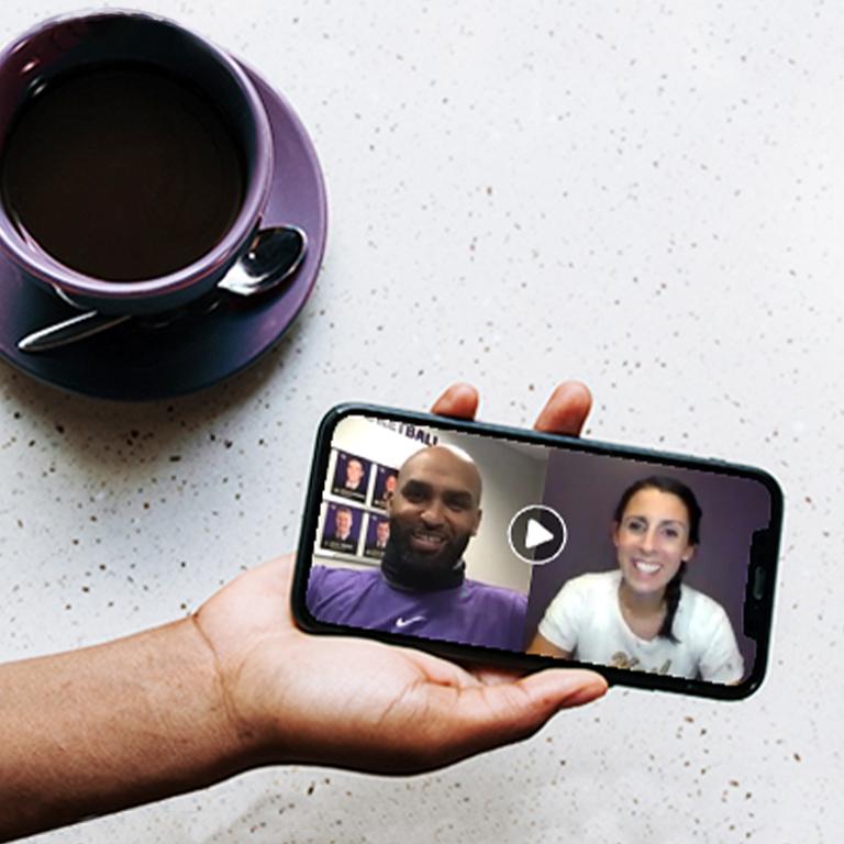 Coffee mug and hand holding phone