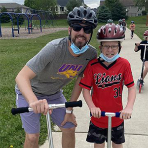 Tanner Roos and student on scooters with bike helmets