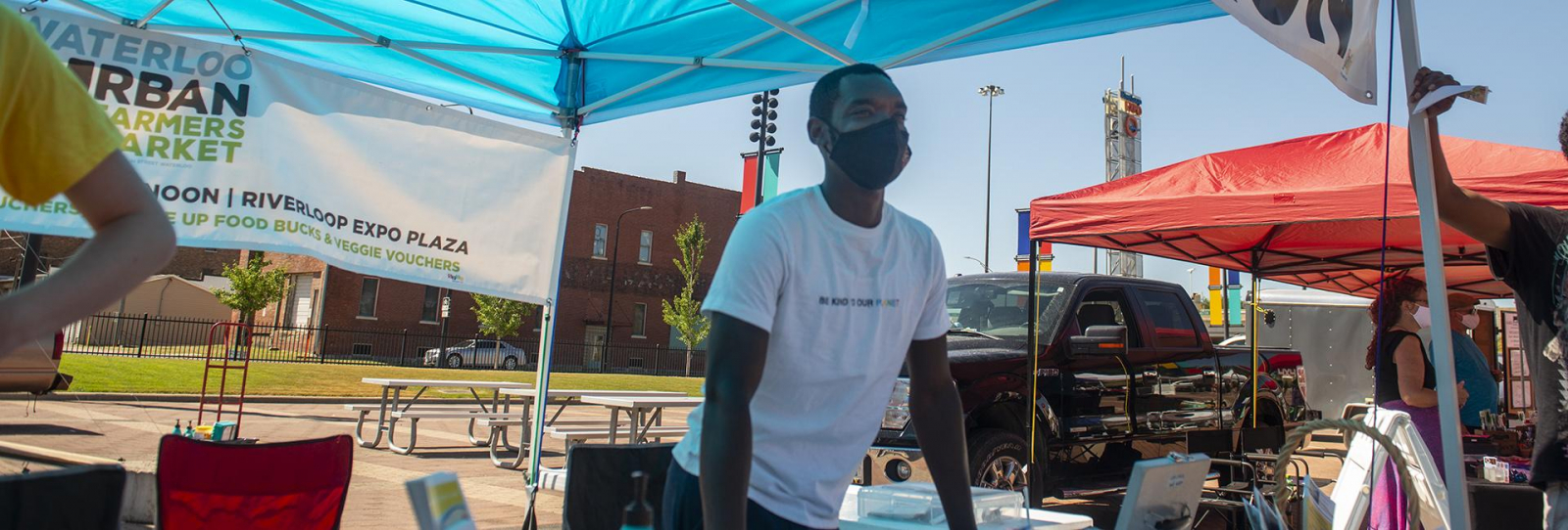 DaQuan Campbell in a white shirt and black mask at a farmer's market
