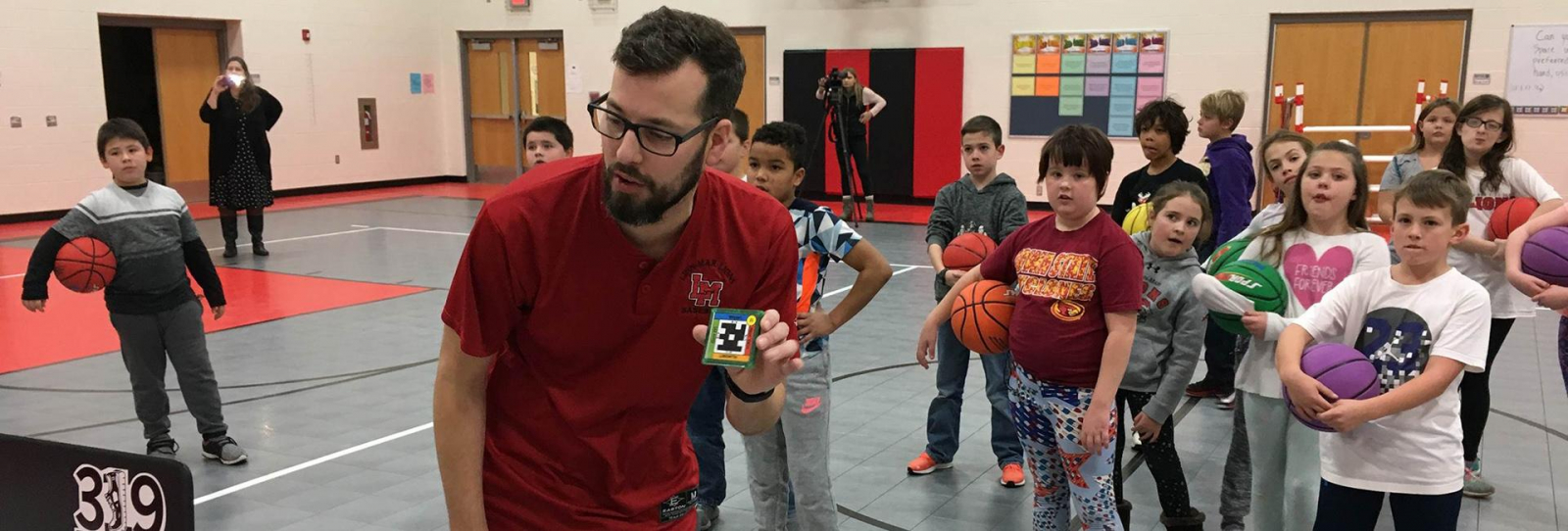 Tanner Roos using a computer with students in physical education class